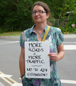 Protester with placard: More roads = more traffic