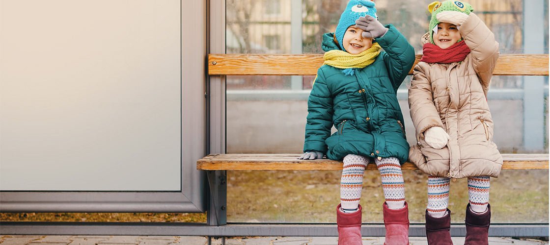 Two children sitting on a bus shelter bench.