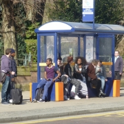 Young people wait at a bus shelter
