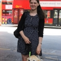 Young woman stands with guidedog, red bus in background