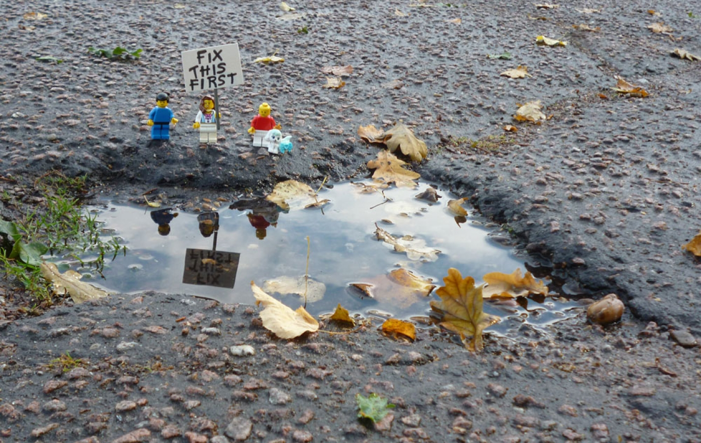 Lego figures by pothole with placard reading 'Fix this first'