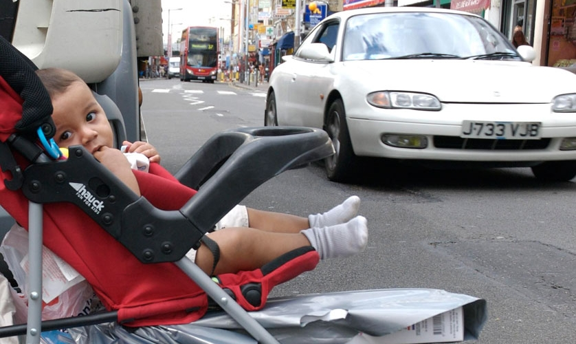 Baby in pushchair close to traffic