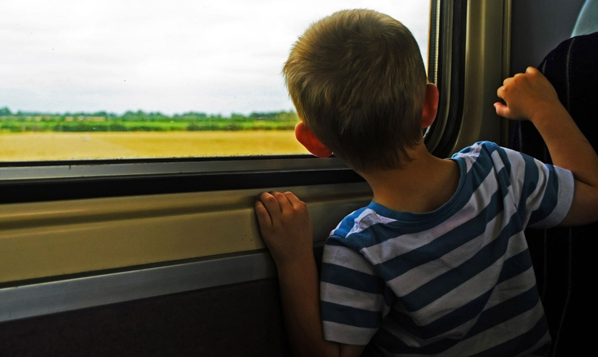 A boy looks out of a train window