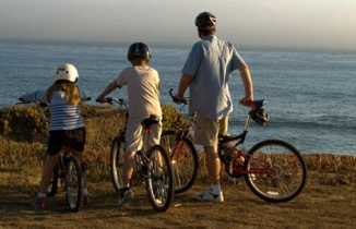 Photo: family on bikes by the sea