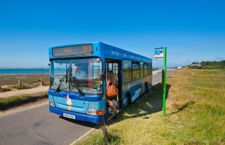 Woman boards a blue single decker Beach Bus