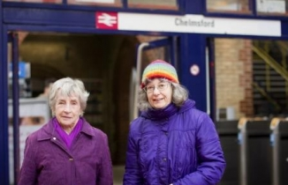 Two older women in bright coats stand outside Chelmsford Station