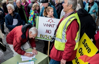 A man signs a petition at a table, with a 'What No Buses' placard in the background