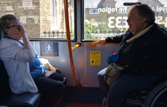 Woman sits on bus opposite wheelchair using man, laughing
