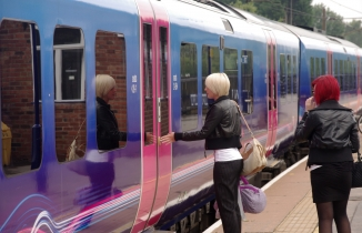 Woman in leather jacket boarding a Thameslink train