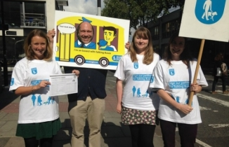 Four people with matching white-blue T shirts stand with placards on a pavement