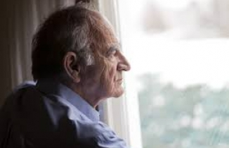 lonely man looking out of a window