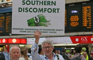 Man holds up a placard reading 'Southern Discomfort'