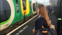 Girl with long hair on platform, green train in background