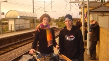 Teenage boy and girl with scarf stand on train platform