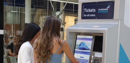 rail passengers buying tickets from a machine