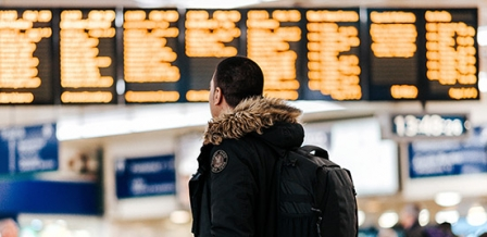 Photo: man in front of departures board