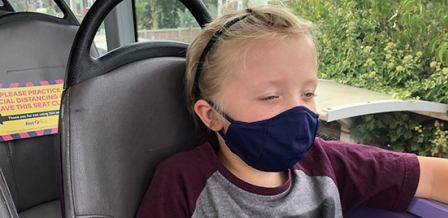 Photo: boy wearing mask on bus