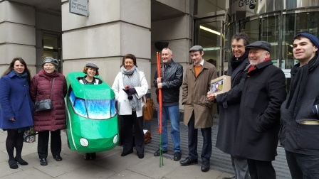 Ten people stand in front of DfT, including one wearing a train outfit